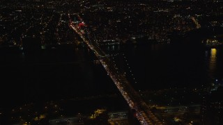 AX122_241 - 6K stock footage aerial video approach and orbit Williamsburg Bridge at Night in New York City
