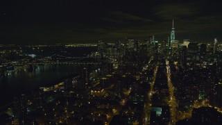 AX122_256 - 6K stock footage aerial video orbit Manhattan Bridge and Lower Manhattan at Night in New York City