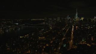 AX122_256E - 5.5K stock footage aerial video orbit Manhattan Bridge and Lower Manhattan at Night in New York City
