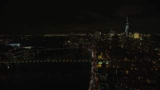 AX122_258 - 5.5K stock footage aerial video of approaching the Manhattan and Brooklyn Bridge in Lower Manhattan at Night in NYC