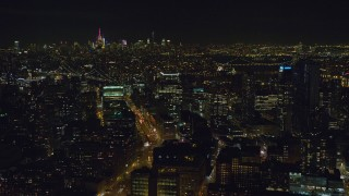 AX122_270 - 6K stock footage aerial video orbit Downtown Brooklyn at Night in New York City with Midtown in the distance
