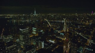 AX122_274 - 6K stock footage aerial video flyby Brooklyn skyscrapers toward East River at Night in New York City