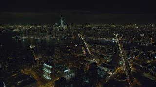 AX122_275 - 6K stock footage aerial video fly over Brooklyn to approach bridges over East River and Lower Manhattan at Night, NYC