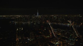 AX122_275E - 5.5K stock footage aerial video fly over Brooklyn to approach bridges over East River and Lower Manhattan at Night, NYC