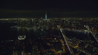 AX122_276 - 6K stock footage aerial video fly over Brooklyn toward Lower Manhattan at Night in New York City