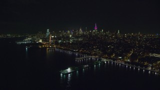 AX122_290 - 6K stock footage aerial video of a wide view of Midtown skyscrapers seen from Greenwich Village at Night in New York City