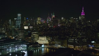 AX122_293 - 6K stock footage aerial video pass riverfront office buildings in Chelsea and Midtown Skyscrapers at Night, NYC