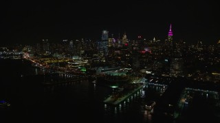 AX122_294 - 6K stock footage aerial video of Chelsea piers and riverfront office buildings at Night in New York City