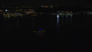 AX123_001 - 6K stock footage aerial video of tracking a small boat on the Hudson River at Night, Union City, New Jersey
