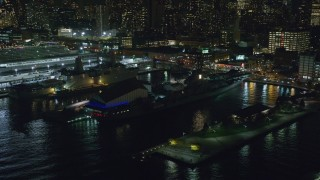 AX123_003 - 6K stock footage aerial video orbit USS Intrepid in Hell's Kitchen, Midtown Manhattan at Night in NYC