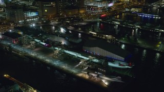 AX123_005 - 6K stock footage aerial video of USS Intrepid docked in Hell's Kitchen at Night in Midtown, New York City