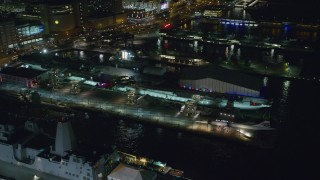 AX123_006 - 6K stock footage aerial video of orbiting the USS Intrepid docked at Hell's Kitchen at Night in Midtown, NYC