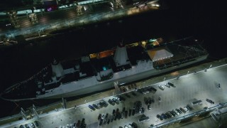 AX123_007 - 6K stock footage aerial video orbit and tilt to bird's eye of a Naval Warship at Hell's Kitchen docks at Night in Midtown, NYC