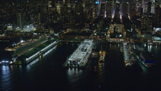 AX123_010 - 6K stock footage aerial video orbit Naval and cruise ships, tilt to Midtown skyscrapers at Night, New York City