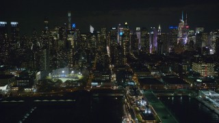 AX123_011 - 6K stock footage aerial video of Midtown skyscrapers seen from a cruise ship docked in Hell's Kitchen at Night, NYC