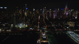 AX123_011E - 5.5K stock footage aerial video of Midtown skyscrapers seen from a cruise ship docked in Hell's Kitchen at Night, NYC