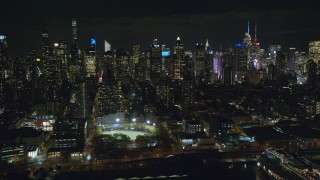 AX123_012 - 6K stock footage aerial video orbit Midtown high-rises and De Witt Clinton Park at Night, New York City