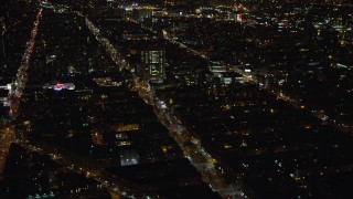 AX123_024E - 5.5K stock footage aerial video orbit city streets and office buildings in Harlem at Night in New York City