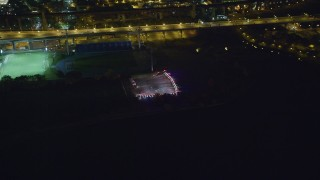 AX123_027 - 6K stock footage aerial video of police cars with bright lights circling a parking lot on Wards Island at Night, New York City