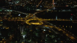 AX123_031 - 6K stock footage aerial video of riverfront freeway interchange by Robert F. Kennedy Bridge at Night, Harlem, New York City