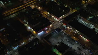 AX123_033 - 6K stock footage aerial video approach and bird's eye of ambulances on a Harlem street at Night in New York City