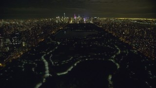 AX123_050 - 6K stock footage aerial video fly over Central Park toward Midtown at Night in New York City