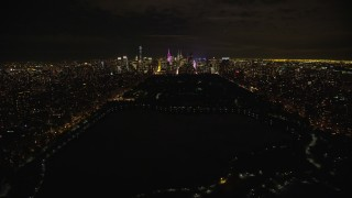 AX123_052E - 5.5K stock footage aerial video fly over Central Park and approach Midtown Manhattan at Night in New York City