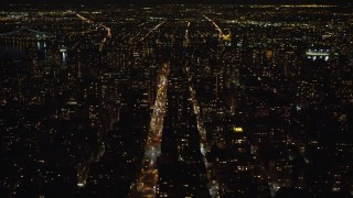AX123_055 - 6K stock footage aerial video of high-rises and streets of Upper East Side at Night in NYC