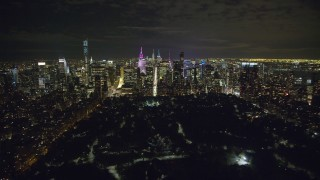 AX123_056 - 6K stock footage aerial video approach Midtown at Night from Central Park in NYC