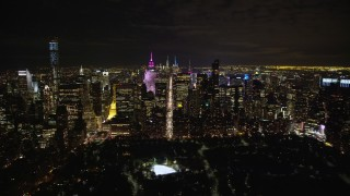 AX123_056E - 5.5K stock footage aerial video approach Midtown at Night from Central Park in NYC