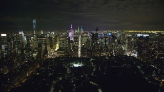 AX123_057 - 6K stock footage aerial video of approaching Midtown from Central Park at Nighttime in New York City