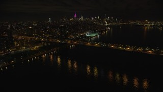 AX123_099 - 6K stock footage aerial video approach the Williamsburg Bridge at Night in New York City