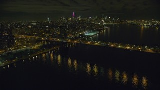 AX123_100 - 6K stock footage aerial video orbiting the Williamsburg Bridge at Night in New York City