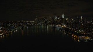 AX123_101E - 5.5K stock footage aerial video approach Manhattan Bridge and Lower Manhattan skyline at Night in New York City