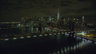 AX123_103 - 6K stock footage aerial video approach Manhattan and Brooklyn Bridges near Lower Manhattan at Night, NYC