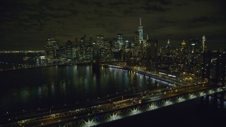 AX123_104 - 6K stock footage aerial video of Manhattan Bridge, Brooklyn Bridge and Lower Manhattan at Night, New York City