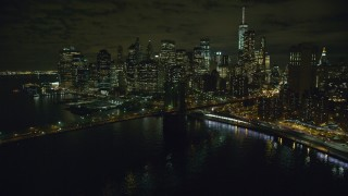 AX123_105 - 6K stock footage aerial video of flying toward the Lower Manhattan skyline and the Brooklyn Bridge at night in NYC