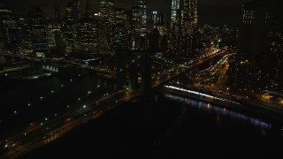 AX123_105E - 5.5K stock footage aerial video of flying toward the Lower Manhattan skyline and the Brooklyn Bridge at night in NYC