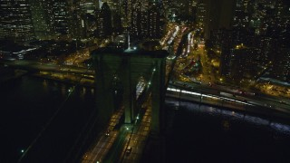 AX123_106 - 6K stock footage aerial video orbit the Manhattan side of the Brooklyn Bridge at Night in NYC