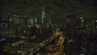AX123_112 - 6K stock footage aerial video orbit Brooklyn Bridge to focus on Lower Manhattan skyscrapers at Night in New York City