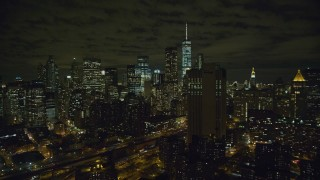 AX123_113 - 6K stock footage aerial video of tall skyscrapers in Lower Manhattan at Night in NYC