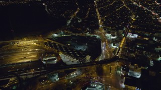 AX123_131 - 6K stock footage aerial video orbit East New York Yard and Bushwick Avenue at Night in Brooklyn, New York City