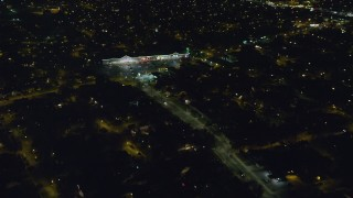 AX123_155 - 6K stock footage aerial video approach suburban strip mall at Night in Hempstead, New York