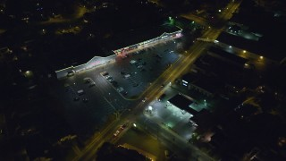 AX123_156 - 6K stock footage aerial video of a small strip mall at Night in Hempstead, New York