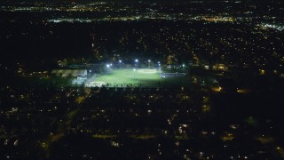 AX123_157 - 6K stock footage aerial video of flying over suburban homes toward baseball fields at Night in Hempstead, New York