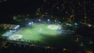 AX123_158 - 6K stock footage aerial video of baseball diamonds at Night in Hempstead, New York