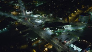 AX123_160 - 6K stock footage aerial video of shops and restaurants in West Hempstead at Night, New York