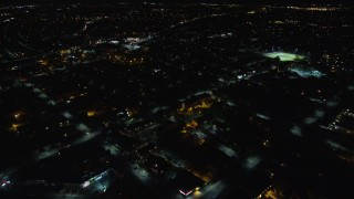 AX123_161 - 6K stock footage aerial video fly over warehouses and suburban homes at Night in Hempstead, New York