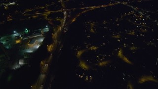 AX123_169 - 6K stock footage aerial video of a reverse view of interchange and Southern State Parkway at Night in Merrick, New York