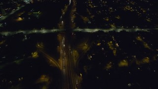 AX123_172 - 6K stock footage aerial video of a reverse view of Southern State Parkway at Night in North Bellmore, New York